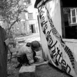 Christian Halbrock, Oppositioneller in der DDR und Mitbegründer der Umwelt-Bibliothek, malt ein Transparent für den Frieden, Friede den Hütten, im Hinterhof des Gemeindehauses in der Griebenowstraße 16.  ©Ann-Christine Jansson